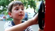 Kid playing with public toy wheel video