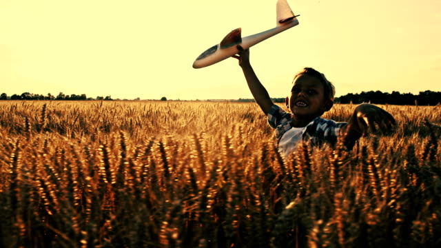 SLO MO Kid running with airplane toy in wheat field video