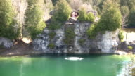 Kids are jumping from cliff into a lake (High Definition) video