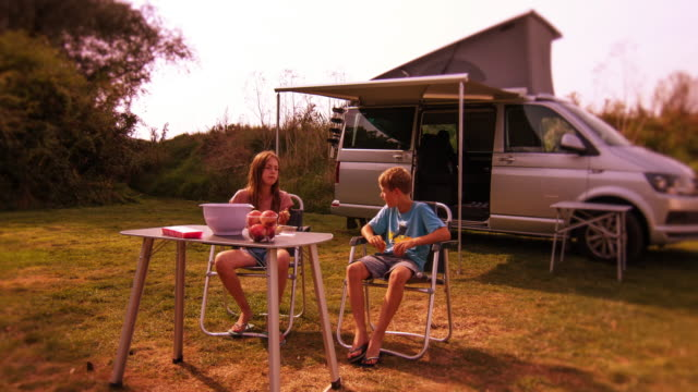 Kids eat and chat by a camper van on a glamping style camping trip. video