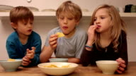 Kids eating corn chips on the kitchen table video
