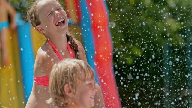 SLO MO Kids enjoying splashing water on a hot day video