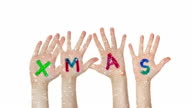 Kid's hands raised up with painted Xmas sign. Christmas background video