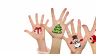 Kid's hands raised up with painted Xmas symbols. Christmas background video