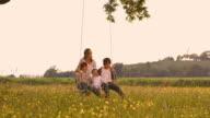 SLO MO Kids having fun swinging on a rope swing video