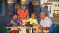 Kids Helping Grandmother to Set Picnic Table video