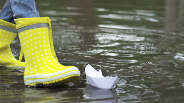 Kids in Rubber Boots Playing with Paper Boats video