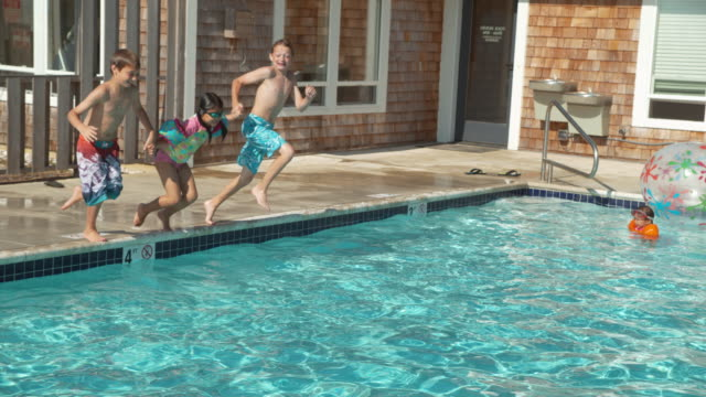 Kids jumping into pool in slow motion video