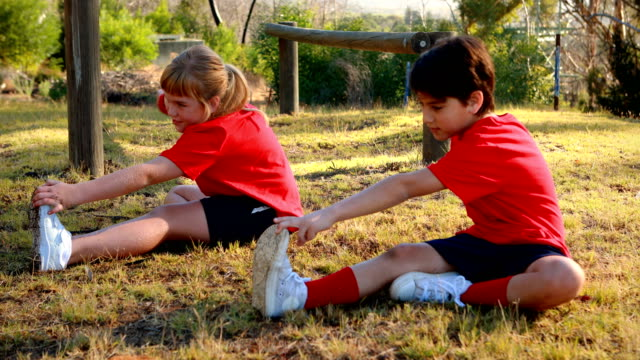 Kids performing stretching exercise in boot camp video