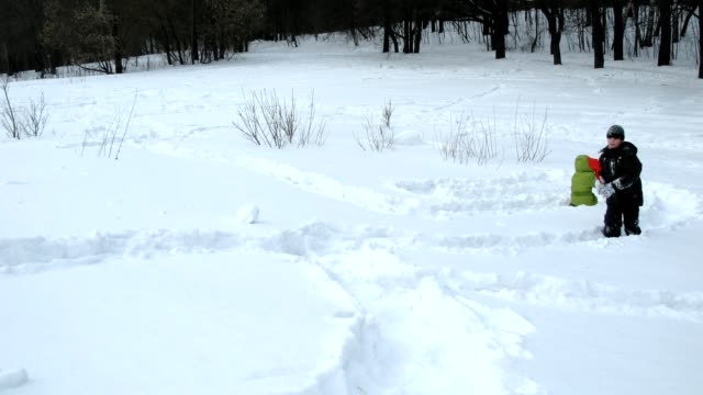 Kids play in snow digging tunnels, time lapse video