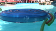 Kids playing in the swimming pool with foam floats. video