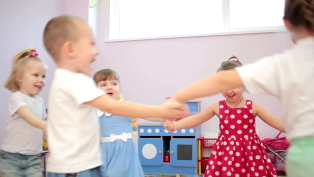 Kids playing running around dancing in kindergarten and laughter video