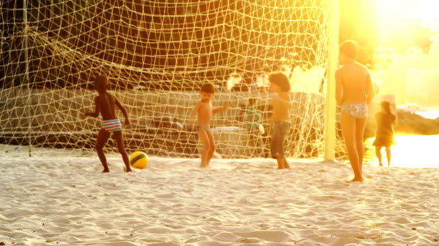 Kids playing soccer on a beach in Brazil video