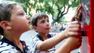 Kids playing with public toy wheel video