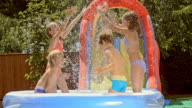 SLO MO Kids splashing water in inflatable pool and laughing video