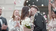 SLO MO Kissing newlyweds being showered with rose petals video