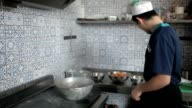 Kitchen worker puts the meat in the pot. video