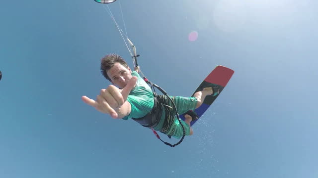 SLOW MOTION CLOSE UP: Kiteboarder jumping and showing shaka sign video