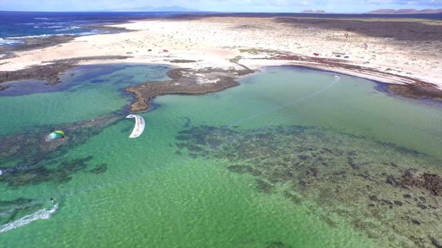 AERIAL: Kiteboarders riding the wind in idyllic lagoon video