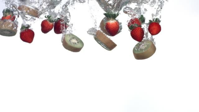Kiwi and strawberries splashing into water video