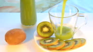 Kiwi juice poured into a glass Cup, pieces of fruit on the plate next. Selective focus. video