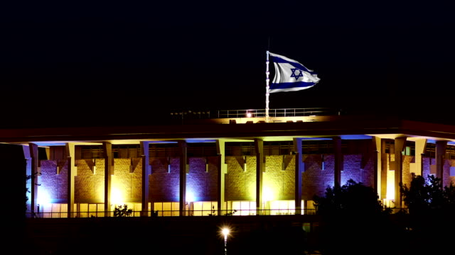 Knesset with flying and waving Israel flag at night video