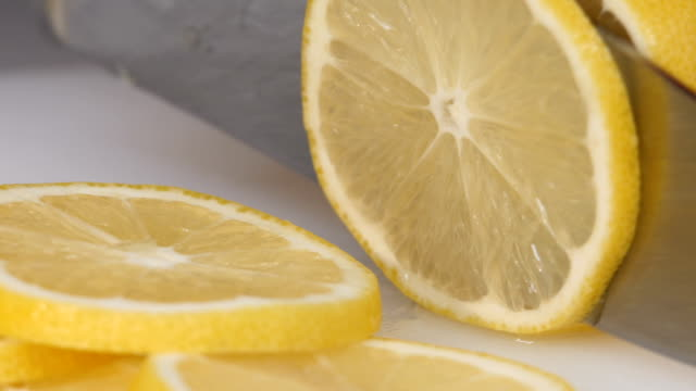 Knife a cutting juicy lemon on white background video