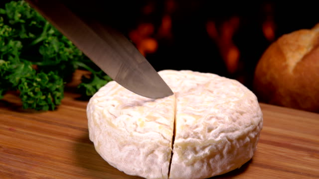 Knife carves a sector of French round cheese video
