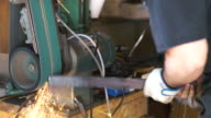 Knife maker grinding down edges on blade video