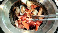Korean barbecue stoves with chacoal, raw shrimp, mussel, fish, bacon video