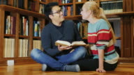 Korean man and Caucasian woman obschayutsya in the library. Smiling video