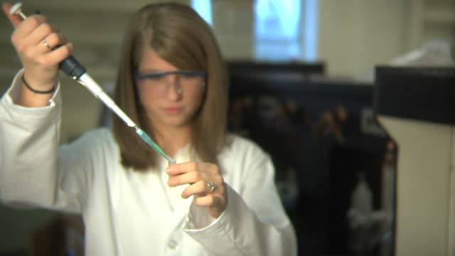 Lab technician fills a test tube with liquid video