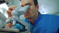 Laboratory researcher using lab microscope. Lab worker looking microscope video