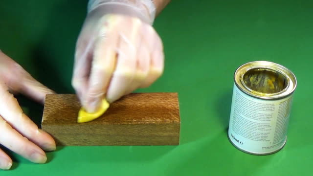Lacewood. The bar of solid wood is covered with stain. The girl covers a bar of rare wood with lacquer. The joinery impregnates the wood with wax. Chroma key video