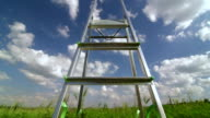 Ladder against blue sky with fluffy clouds video