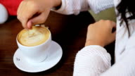 Lady in a white pulloverholding a teaspoon and stirring prepared hot delicious  coffee with milk in a white cupat coffee shop. video