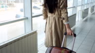 Lady in beige coat with black hair carries suitcase video