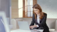 Lady in business suit, glasses works on laptop, smiles at video