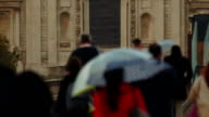A lady in red walking along a group of anonymous people in Central London on a rainy day video