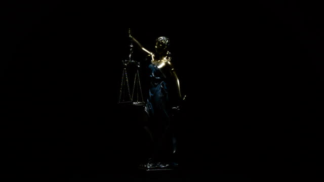 Lady justice gyrating over black background video