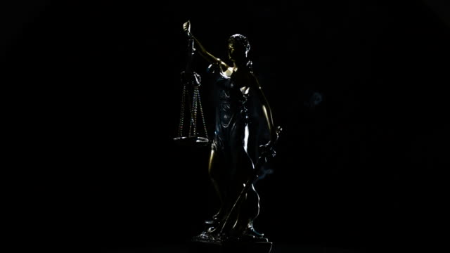 Lady justice in rotation over black background with strands of smoke video