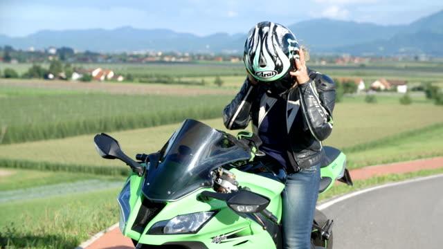 Lady on a motorbike taking off her helmet video