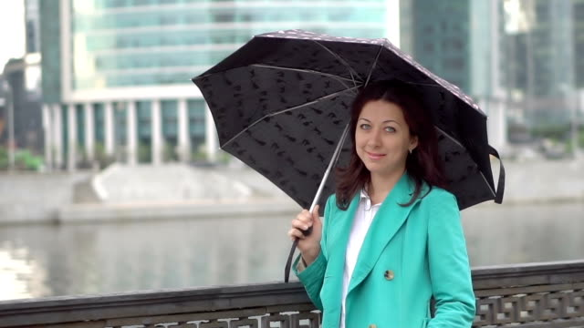 Lady stands in the rain with umbrella in hand video