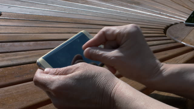A Lady Using Mobile Phone On A Brown Wooden Table video