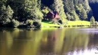 Lake with forest and wood hut video