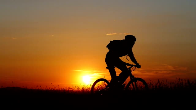 Landscape at sunset and mountain biker riding video