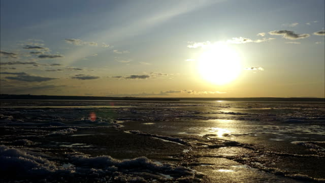 Landscape of a large lake at sunset. Small waves roll on the sandy shore. The red sun is visible on the horizon line. The clouds are colored red. A quiet summer evening. video