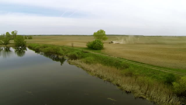 Landscape with  plowing tractor and  river. Aerial  nature  view video