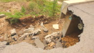 landslide below asphalt road, next to a bridge video
