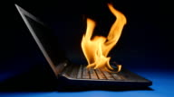 SLOW MOTION: Laptop flaming on a table - Side view video